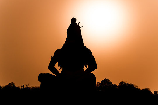 A silhouette of a statue of the Hindu god Shiva on the banks of the Ganges at Rishikesh in North India.