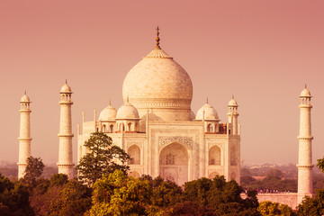 The Taj Mahal as seen over the treeline from a distance with a warm tone.