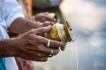Hands pouring sacred water into a river during  daily worship