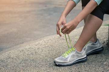 closeup of woman tying shoe laces.