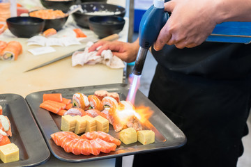 Torch burner over sushi rolls. Man's hand holding torch burner. Chef prepares uramaki sushi.