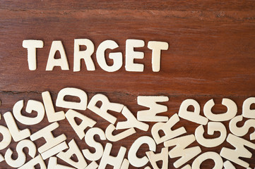 Word target made with block wooden letters next to a pile of other letters over the wooden board surface composition