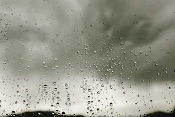 raindrops on window glass on background of gray clouds, rainy we