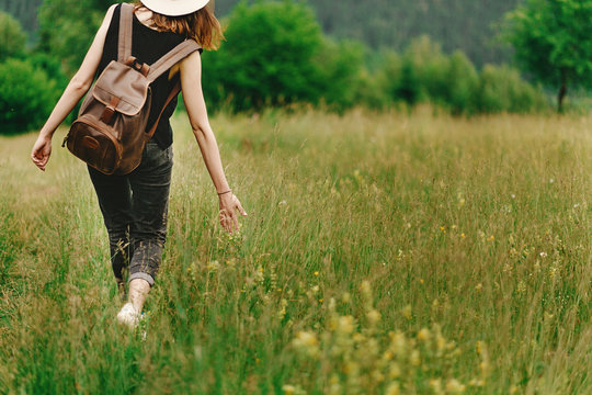 stylish hipster woman walking in grass and holding  in hand herb