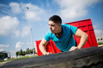 Concentrated athlete doing push-ups on tyre