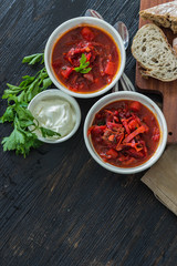 Ukrainian beetroot soup - borscht, on napkin, on wooden background.  Top view with copy space.