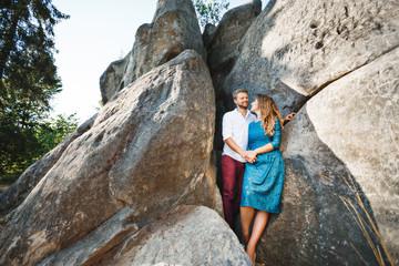 Smiling couple standing near rocks