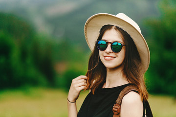stylish hipster woman  in hat and sunglasses smiling on backgrou