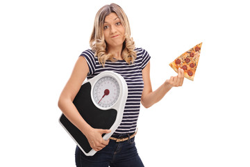 Woman holding slice of pizza and weight scale