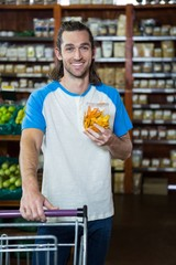 Man holding grocery item with shopping trolley