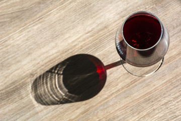 One glass of red wine on the brown wooden background with shadow