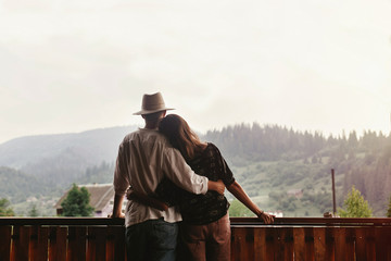 hipster couple hugging on porch of wooden house looking at mount