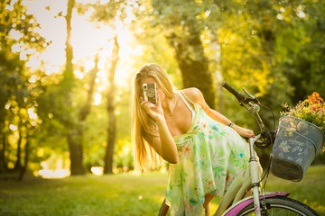 Portrait of female on vintage bicycle taking a photo with retro camera in nature. Summer, lifestyle and fashion concepts.