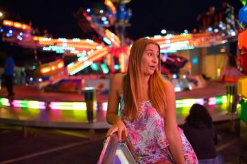 Pretty girl against of bright illuminated carousel