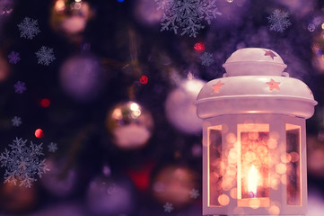 Christmas, New Year lantern with a candle and a blurred image of toys on the Christmas tree in the background. Lovely festive Christmas background.