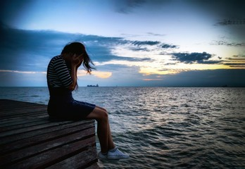 Beautiful woman in frustrated depression sitting on wooden bridge, near the beach on sunset. Concept of unemployed, sadness, depressed and human problems in dark tone.