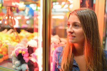 smiling girl looking away against of attraction with toys