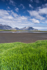 Summer landscape with green grass and mountains in Iceland
