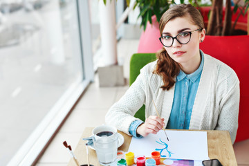 Girl with glasses sitting with colorful paints
