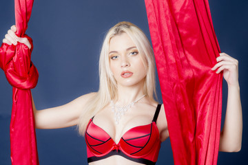 Gentle portrait of a woman with red curtains. The girl in the bra with her long blonde hair.