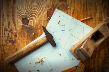 Equipment carpenter and plans to build on a wooden wooden background