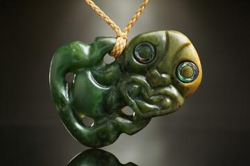 Hei Tiki Symbol Schmuck der Maori aus Neuseeland. Handarbeit aus neuseeländischer Jade mit Augen Details aus einer Abalone Meeresschnecke.
