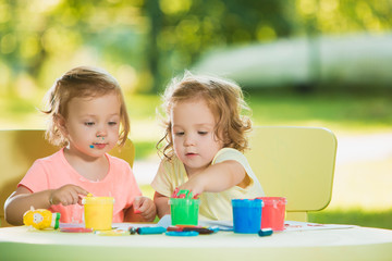 Two-year old girls painting with poster paintings together against green lawn