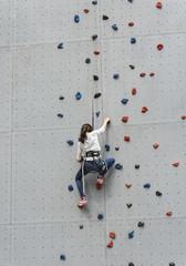 Jeune fille grimpant sur mur d'escalade