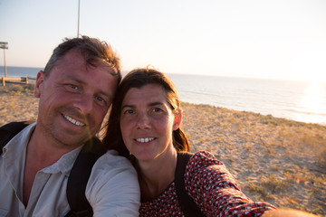 Happy couple taking selfie photo with a smart phone at sunset on the beach