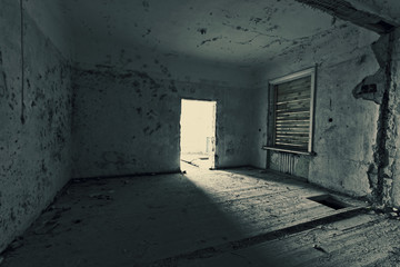 Dark room in an abandoned ruined house. Grunge texture. Tinted photo.