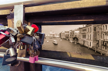 Close up of love symbol padlocks on a bridge of Venice, with Grand Canale background