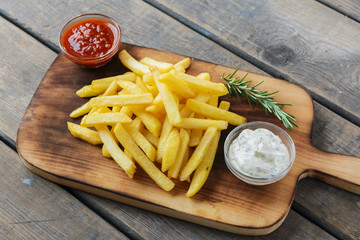French fries with sauce on a cutting board