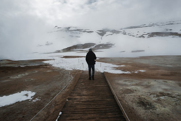 Man walking in path in natural baths in Iceland