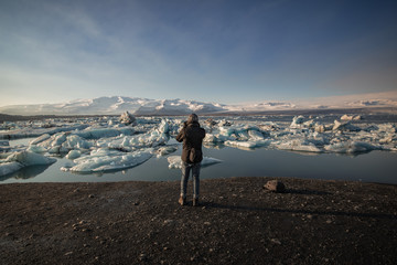 Man taking photographs in jokulsarlon in Iceland