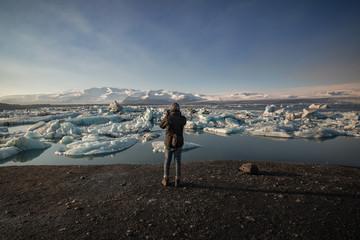 Rear view of man taking photograph at Jokulsarlon Lake