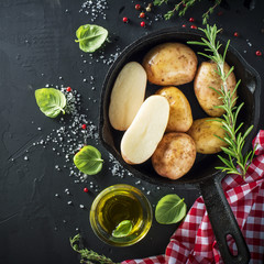Young ripe potatoes in a black cast iron pan with herbs, olive oil, rosemary, pepper, sea salt for baking. Healthy homemade food, Vegetarian and diet.