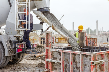 Zrenjanin, Vojvodina, Serbia - May 21, 2015: Workers at building site are pouring concrete in mold from mixer truck. Pouring reinforced concrete in foundation mold