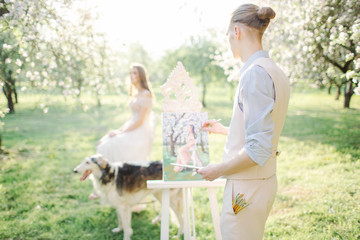Artist with watercolor painting of bride in wedding dress outdoo