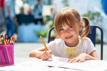 Little beautiful girl draws pencil
