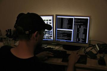 Computer Hacker blickt auf zwei Monitore
