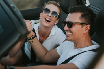 cheerful family couple lovers smiling and cheating to each other driving a cabriolet and searching the location they need by pointing on car gps system
