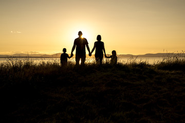 family of four at sunset shadow black backlit