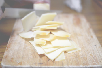 Slicing some cheese on a wooden table in a rustic kitchen.