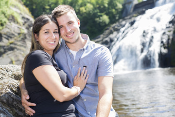 Young couple in love with waterfall on background