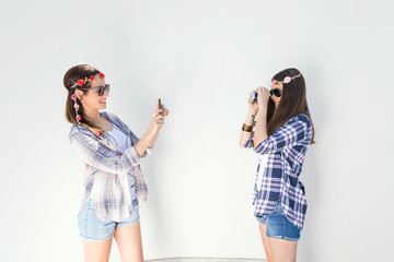 Young friends are having fun taking photos of each other. One of them is using smart phone and the other is using vintage camera. Girls are wearing matching outfits, plaid shirts and denim shorts.
