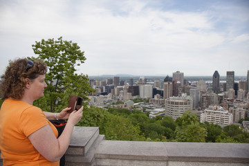woman taking picture of Montreal city with cell phone on top of