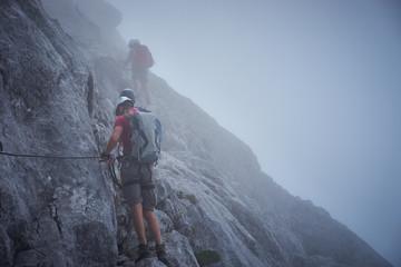 Men climbing in foggy mountains / Dangerous ferrata trail in Austria
