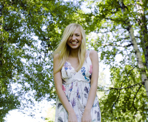 happy blond young woman in park smiling, floral close up
