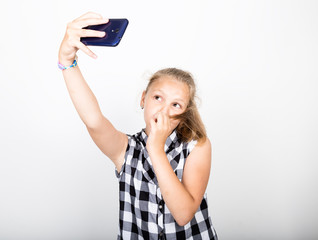 Portrait of happy beautiful young girl makes salfie, expresses different emotion