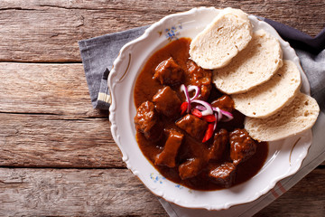 homemade hot Czech goulash with knodel close-up. horizontal top view